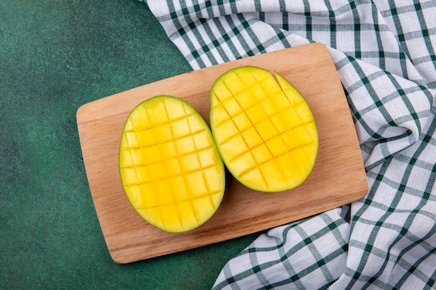 Top view of yellow delicious and exotic mango slices on a wooden kitchen board on checked tablecloth and green surface