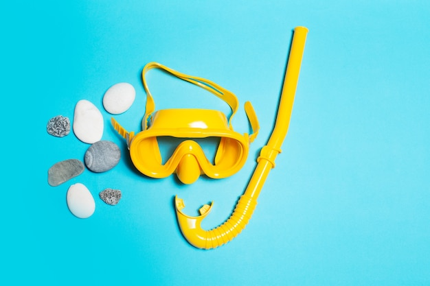 Top view of yellow diving mask with snorkel near stones  background.
