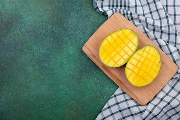Top view of yellow exotic fresh mango slices on a wooden kitchen board on checked tablecloth and green surface