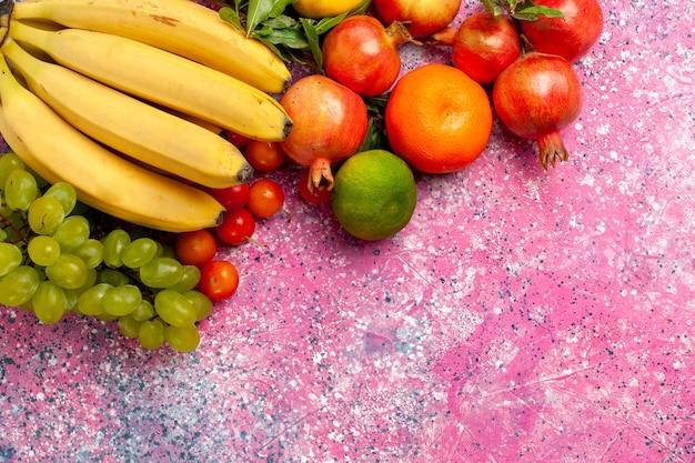 Вид сверху желтые свежие бананы, вкусные фрукты с виноградом и гранатами на розовом столе