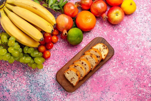 Top view yellow fresh bananas delicious fruit with grapes cakes and pomegranates on pink desk