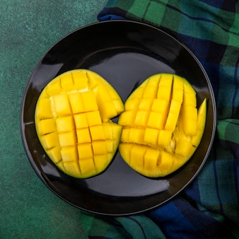 Top view of yellow fresh delicious mango slices in a black plate on checked tablecloth and green surface