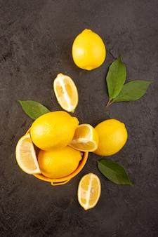 Una vista dall'alto giallo limoni freschi morbidi e succosi interi e affettati all'interno del cestino giallo diffuso con foglie verdi su sfondo scuro frutti colore agrumi