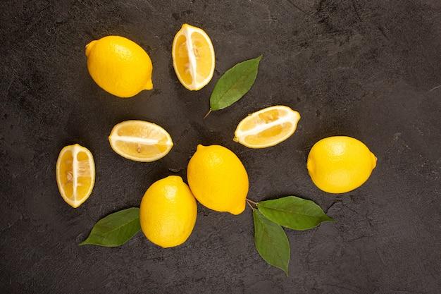 Una vista dall'alto giallo limoni freschi morbido e succoso intero e affettato con foglie verdi su sfondo scuro frutti di colore di agrumi
