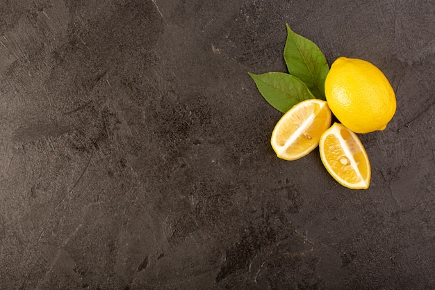 A top view yellow fresh lemons mellow and juicy whole and sliced with green leaves on the dark background fruits citrus color