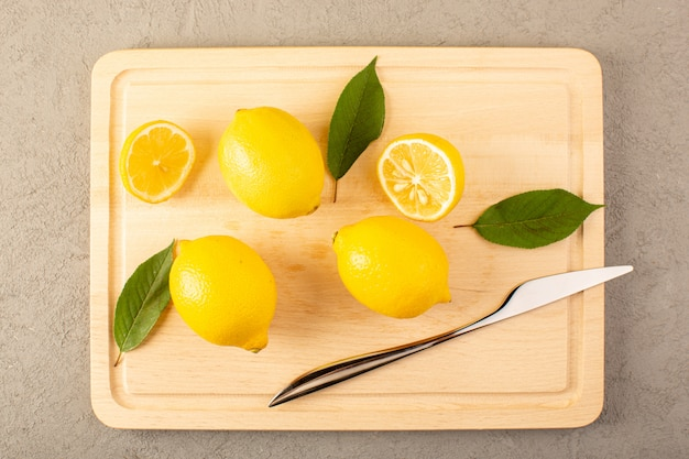 A top view yellow fresh lemons ripe mellow juicy with green leaves surfaced on the cream desk lined and sliced on the grey background fruits citrus color