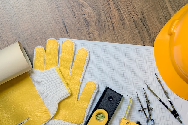 Top view of yellow glove and drawing tools on wooden table, copy space.