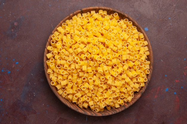 Top view yellow italian pasta raw little formed on dark background pasta food raw meal dough