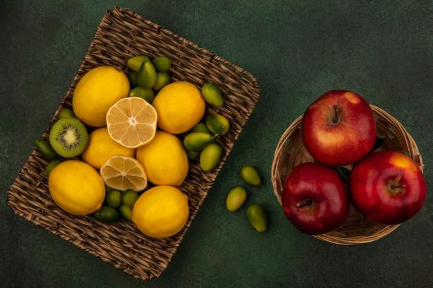 Vista dall'alto di limoni gialli su un vassoio di vimini con kinkans con mele rosse su un secchio su una parete verde