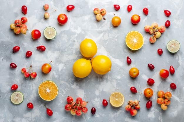 Limoni gialli di vista superiore con le ciliege sullo scrittorio bianco