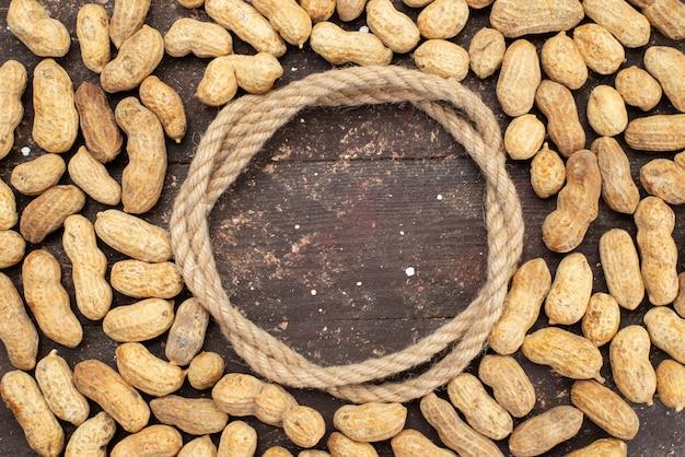Вид сверху желтые орехи с веревкой на коричневый, орех ореховая закуска соль