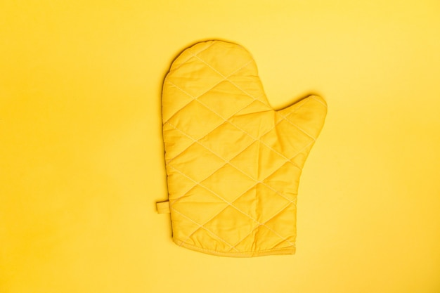 Top view of yellow oven gloves on yellow color background.