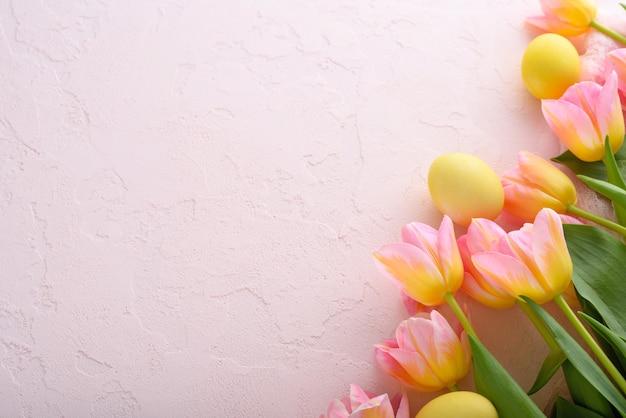 コピースペースとピンクの背景にピンクのチューリップと黄色のパステルイースターエッグの上面図