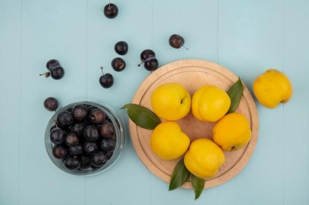 Vista dall'alto di pesche gialle su una tavola da cucina in legno con prugnole acide viola scuro su una ciotola di vetro su sfondo blu