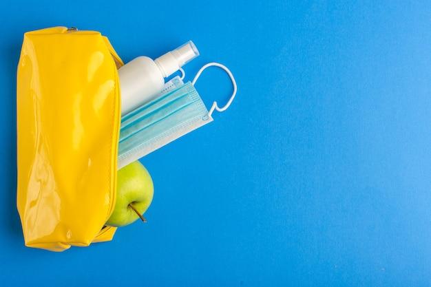 Scatola di penna gialla vista dall'alto con mela spray e maschera sulla superficie blu