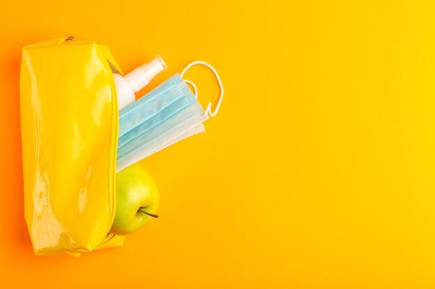 Scatola di penna gialla vista dall'alto con mela spray e maschera sulla superficie arancione