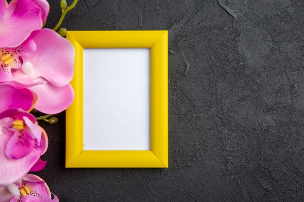 Top view yellow photo frame pink flowers on dark free space