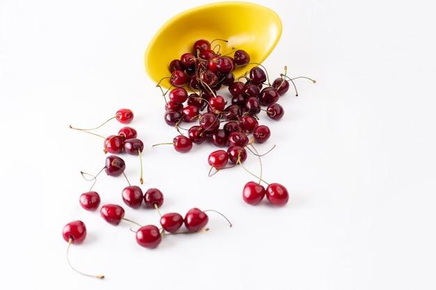 Piatto giallo di vista superiore con le ciliege rosse aspre fresche sul succo pastoso di colore della frutta del fondo bianco
