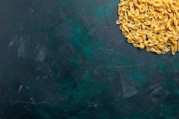 Pasta italiana di pasta cruda gialla vista dall'alto sulla scrivania blu scuro