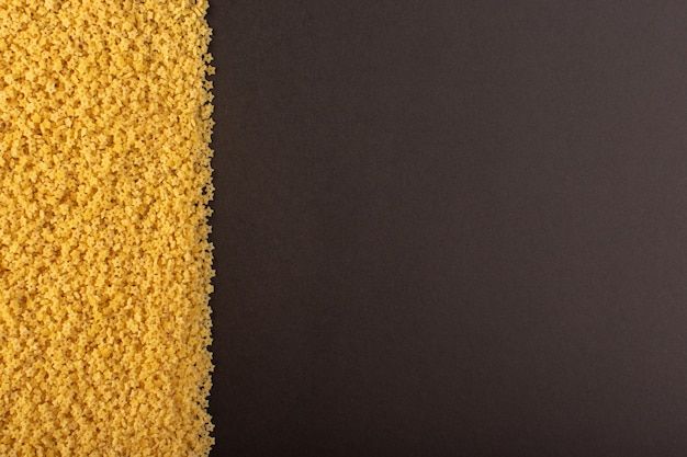 A top view yellow raw pasta on the left side dark background food meal raw eating