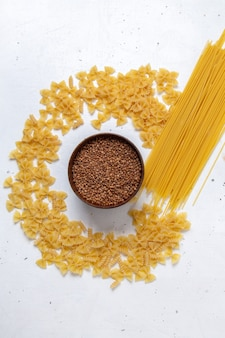 Top view yellow raw pasta little formed and long with plate of buckwheat on the white desk pasta italy food meal