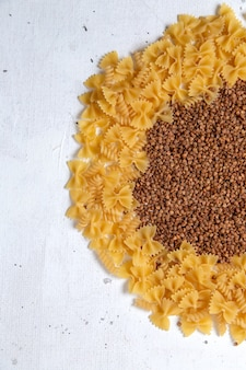 Top view yellow raw pasta little formed with buckwheat on the white desk pasta italy food meal