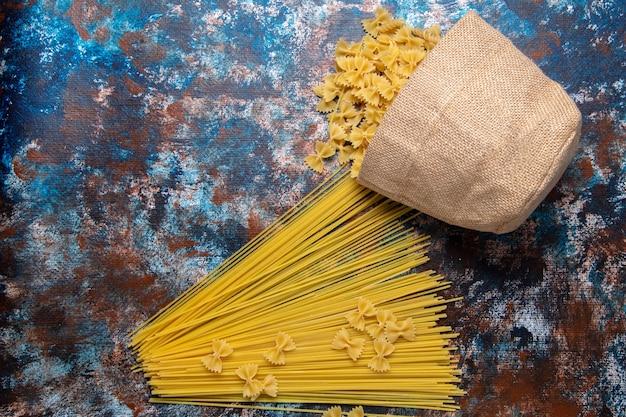 Vista dall'alto giallo pasta cruda lunga formata e poco dappertutto sfondo colorato pasta italia cibo pasto