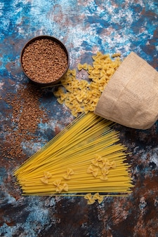 Top view yellow raw pasta long formed and little with buckwheat all over the colored background pasta italy food meal
