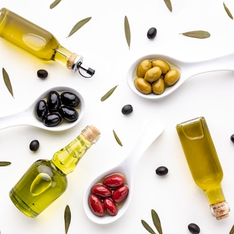 Top view yellow red black olives in spoons  with leaves and oil bottles