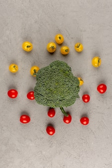 Top view yellow red tomatoes along with green broccoli on the grey background