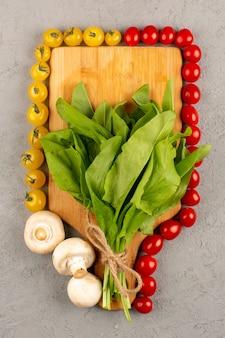 회색 바닥에 녹색과 함께 잘 익은 상위 뷰 노란색 빨간 토마토 신선한 잎