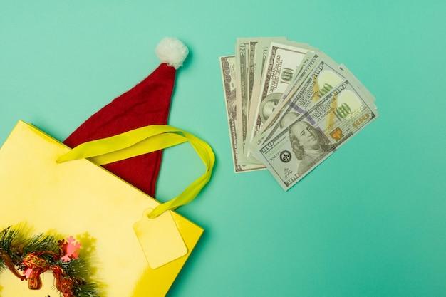 Вид сверху желтая сумка для покупок с новогодней шапкой и деньгами на столе с праздничным сезоном