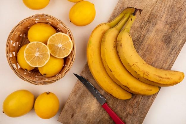 Vista dall'alto di limoni dalla pelle gialla su un secchio con banane isolato su una tavola da cucina in legno con coltello su un muro bianco
