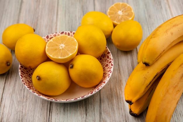 Vista dall'alto di limoni interi dalla pelle gialla su una ciotola con le banane isolate su un fondo di legno grigio