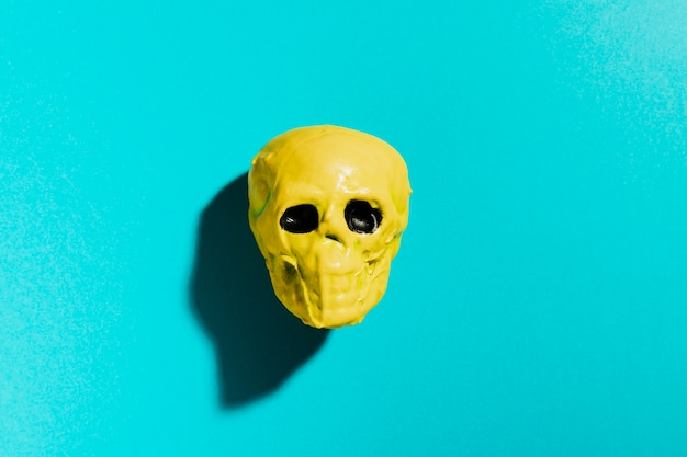 Top view yellow skull on blue background