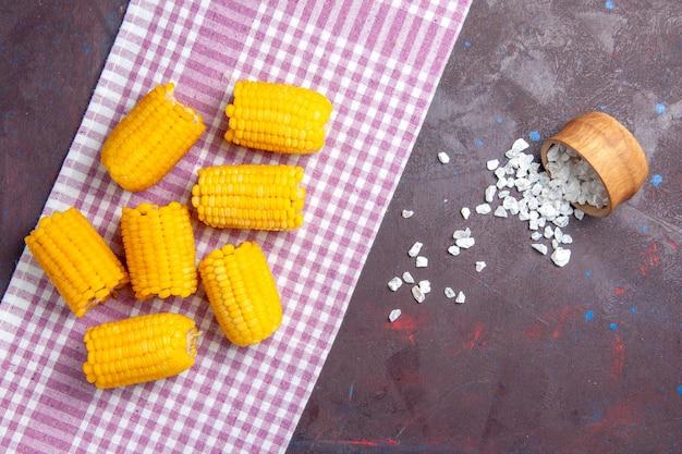 上面図黄色のスライスしたトウモロコシの生と新鮮な暗い背景のトウモロコシ植物食品生の新鮮