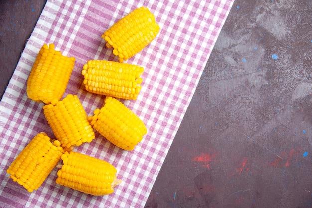 상위 뷰 노란색 얇게 썬 옥수수는 어두운 배경 옥수수 식물 식품 생으로 신선하고 신선합니다.