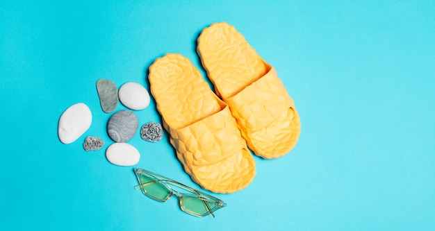 Top view of yellow slippers and sunglasses near pebbles  background.