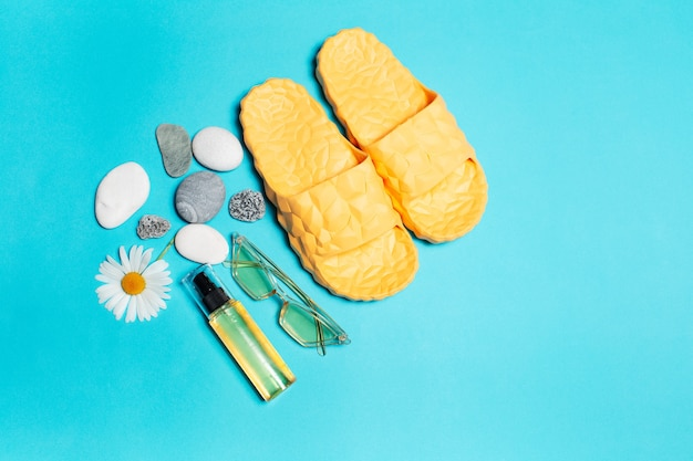 Top view of yellow slippers, sunglasses and oil tube decorated with chamomile flower and pebbles