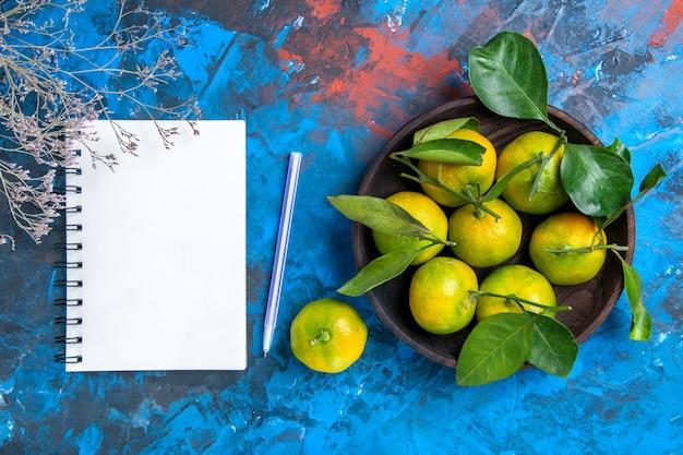 Вид сверху желтые мандарины с листьями в деревянной миске, блокнот и фиолетовая ручка на синей поверхности