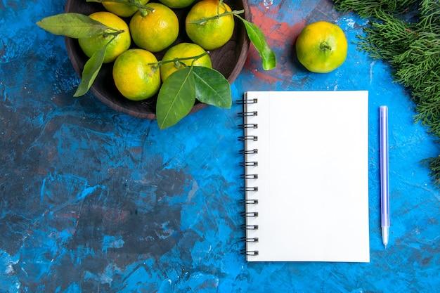 Вид сверху желтые мандарины с листьями в деревянной миске, блокнот, фиолетовая ручка на синей поверхности, свободное пространство