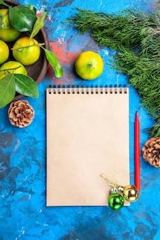 Mandarini gialli di vista superiore con i fogli in ciotola di legno un ornamento rosso di natale della matita del taccuino sulla superficie blu