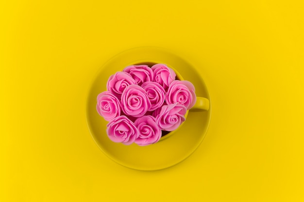 Top view yellow tea mug full of pink flowers on yellow