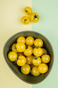 Top view of yellow tomatoes in bowl on yellow and green table