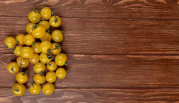 Top view of yellow tomatoes on left side and wooden table