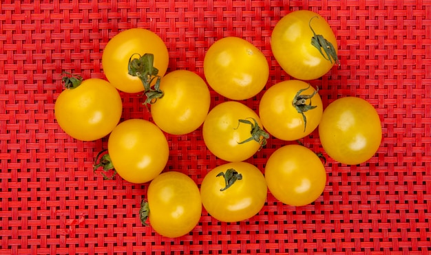 Top view of yellow tomatoes on red cloth table