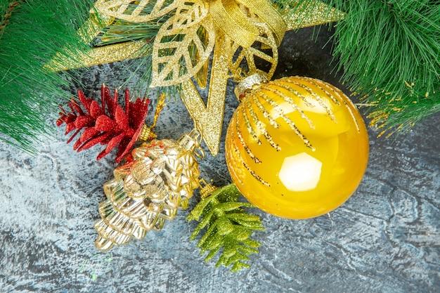 Vista dall'alto ciondoli di natale con palla di albero di natale giallo su superficie grigia