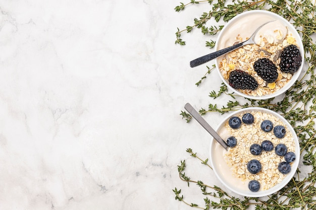 Top view yogurt with fruits and oats with copy-space