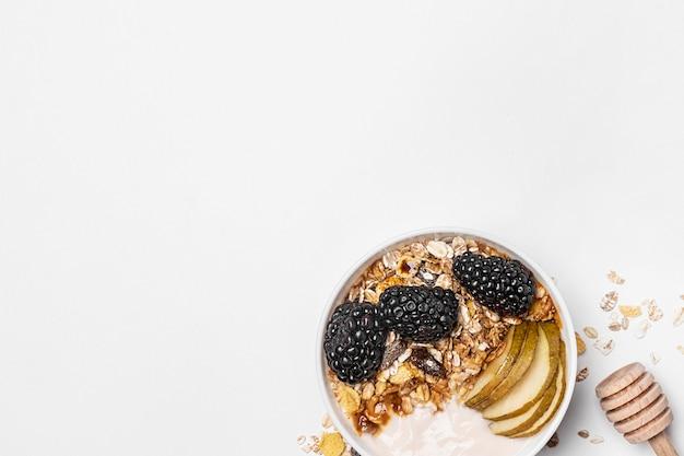 Вид сверху йогурт с овсом, фруктами и медом с копией пространства