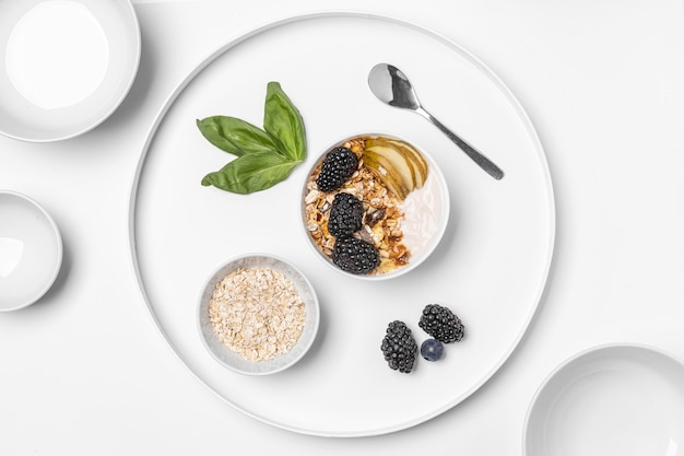 Top view yogurt with oats, fruits and honey on plate